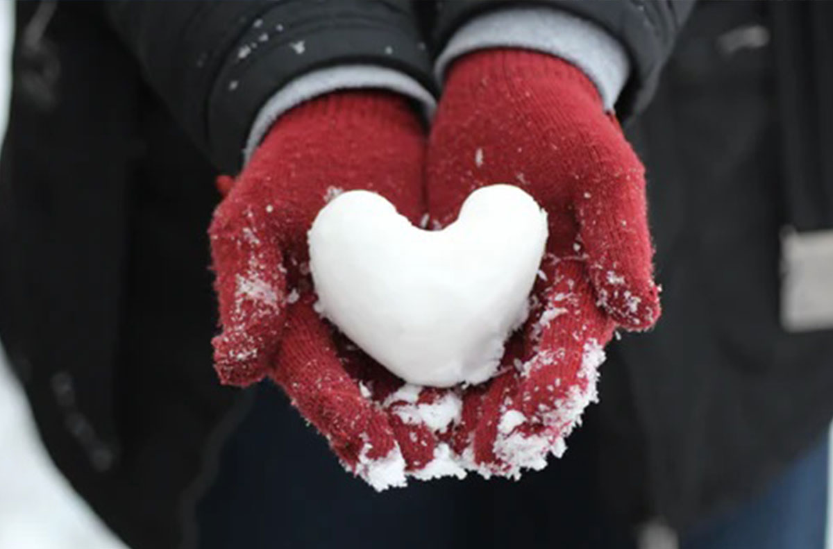 Gloved hands hold snow heart